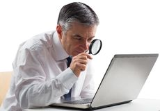 Mature businessman examining with magnifying glass Stock Photography