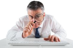 Mature businessman examining with magnifying glass Royalty Free Stock Photo