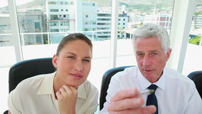 Mature businessman explaining something to a young woman stock footage