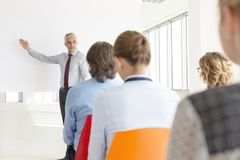 Mature businessman explaining strategy to colleagues during meeting at office stock photography