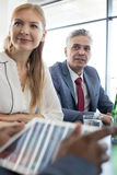 Mature businessman with female colleague at table in meeting room Royalty Free Stock Photos