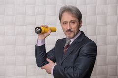 Mature businessman with flashlight Stock Images