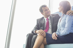 Mature businessman flirting with female colleague in office Royalty Free Stock Images