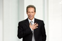 Mature businessman with hand on chest. Pledge promise of caucasian man in business suit. Portrait of swearing man in formal wear stock images