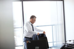Mature businessman hanging jacket on back of office chair Royalty Free Stock Photo
