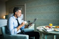 Mature businessman having breakfast in a hotel room. royalty free stock images