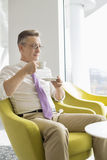 Mature businessman having coffee in lobby at office Royalty Free Stock Photo