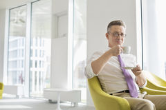 Mature businessman having coffee at office lobby Royalty Free Stock Photography