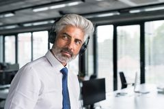 Mature businessman with headphones in the office. Royalty Free Stock Photography