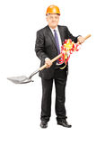 Mature businessman with helmet holding a shovel with ribbon Royalty Free Stock Photography