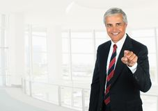 Mature businessman in high key office setting pointing at the camera stock image