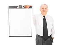 Mature businessman holding blank paper on clipboard Stock Photos