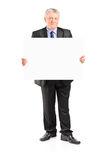 Mature businessman holding a blank poster Royalty Free Stock Photos