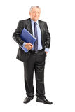 Mature businessman holding a blue folder. Full length portrait of a mature businessman holding a blue folder and looking at the camera isolated on white stock images