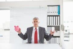 Mature businessman holding coffee and piggy bank Stock Photos