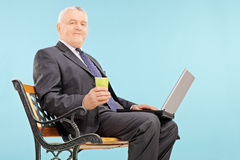 Mature businessman holding a cup and laptop Royalty Free Stock Photography