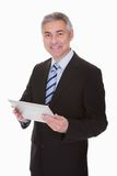 Mature businessman holding digital tablet stock image