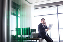 Mature businessman holding document while talking on mobile phone in office Royalty Free Stock Images