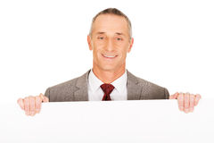 Mature businessman holding empty banner Royalty Free Stock Photo