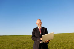 Mature Businessman Holding Laptop On Field Royalty Free Stock Photo