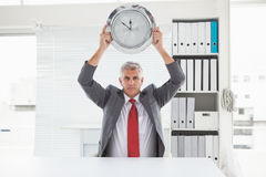 Mature businessman holding large clock Stock Photo