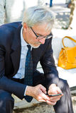 Mature businessman holding mobile phone and looking a Royalty Free Stock Images