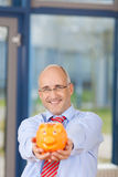 Mature Businessman Holding Piggybank In Office Royalty Free Stock Photography
