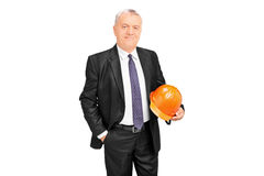 Mature businessman holding a protective helmet Stock Photo
