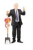 Mature businessman holding a shovel and giving thumb up Stock Images
