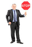 Mature businessman holding a stop sign Stock Images