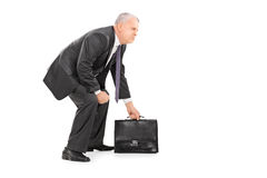 Mature businessman holding suitcase and standing in sumo wrestli Royalty Free Stock Photos