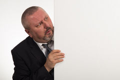 Mature businessman holding a white panel and gesturing isolated on white background.  Stock Photos