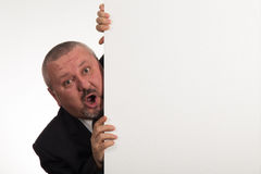 Mature businessman holding a white panel and gesturing isolated on white background Stock Image