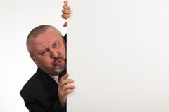 Mature businessman holding a white panel and gesturing isolated on white background Royalty Free Stock Photos
