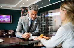 Mature businessman at hotel reception. royalty free stock images