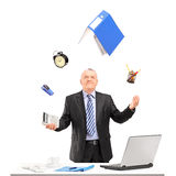 Mature businessman juggling in his office. Isolated on white background Stock Photos