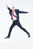 Mature businessman jumping. Happy mature businessman jumping on white Royalty Free Stock Image