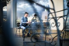 Mature businessman with laptop in an outdoor hotel cafe. Royalty Free Stock Photography
