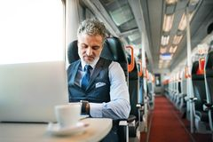 Mature businessman with laptop travelling by train. Handsome mature businessman with laptop travelling by train. A man with smartwatch, checking the time Royalty Free Stock Photos