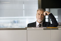 Mature businessman leaning on filing cabinet in office, portrait Royalty Free Stock Images