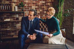 Mature businessman listening answer about inkblot picture. Attentive psychologist is sitting near client. She explaining meaning of image from rorschach test Royalty Free Stock Image