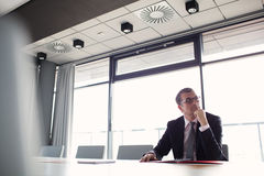 Mature businessman listening to meeting in board room.  Royalty Free Stock Photo