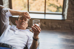 Mature businessman looking at glass with alcohol Royalty Free Stock Images