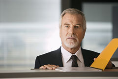 Mature businessman looking at orange file in office, front view, portrait Stock Photos