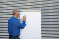 Mature Businessman Making  Presentation On Flipchart Royalty Free Stock Photos