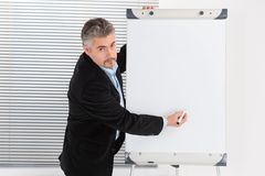 Mature businessman making presentation on flipchart. Stock Photography