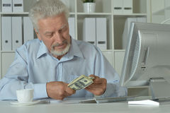 Mature businessman with money. Portrait of a mature businessman in office with money Royalty Free Stock Images