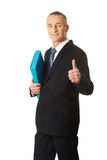 Mature businessman with ok sign holding a binder Stock Photo