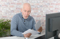 Mature businessman opening letter envelope. With astonishment Royalty Free Stock Images