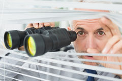 Mature businessman peeking with binoculars through blinds Royalty Free Stock Images